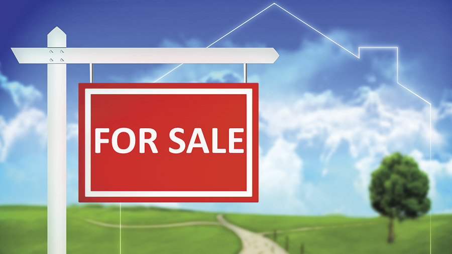 A red For Sale sign with land behind